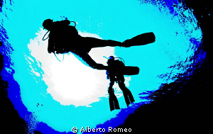 Divers in backlight by Alberto Romeo 